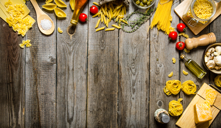 Pasta background. Several types of dry pasta with vegetables, cheese and herbs. On a wooden table.  Free space for text . Top view