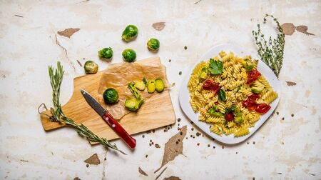 vegetarian food: Pasta with Brussels sprouts, herbs and spices. On rustic background.  Top view