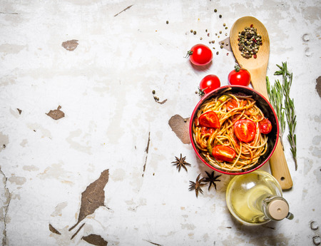 spaghetti dinner: Spaghetti with tomato paste, olive oil and spices.  On rustic background.  Free space for text . Top view