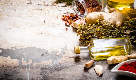 A set of dried spices and herbs with olive oil. On rustic background. Free space for text .