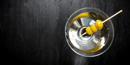 Uống martini. Martini với ô liu trên một bảng đen. Miễn phí không gian cho văn bản. Top xem