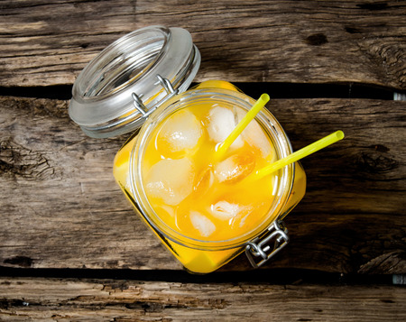 alcohol screwdriver: Fresh orange cocktail . Cocktail with ice in a jar with straw on wooden background . Top view Stock Photo