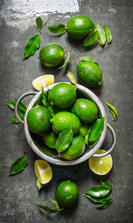 citricos: fondo de la cal. limas frescas en una cacerola con las rebanadas y las hojas alrededor. En la mesa de piedra. Vista superior