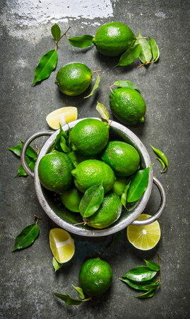 Lime background. Fresh limes in a saucepan with slices and leaves around. On the stone table. Top view Stock Photo