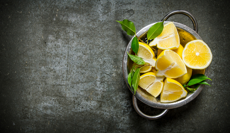 lemon: Fresh sliced lemons with leaves in a saucepan. On the stone table. Free space for text . Top view