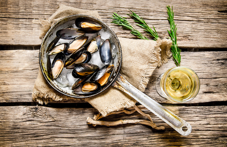 Fresh clams in a pan with the wine. On wooden background. Top view