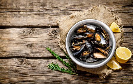 limon: Cup with clams, Limon and rosemary. On a wooden table.  Free space for text . Top view Stock Photo