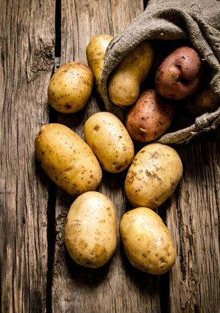 원시 감자 음식입니다. 나무 배경에 오래 된 자루에 신선한 감자. 스톡 콘텐츠