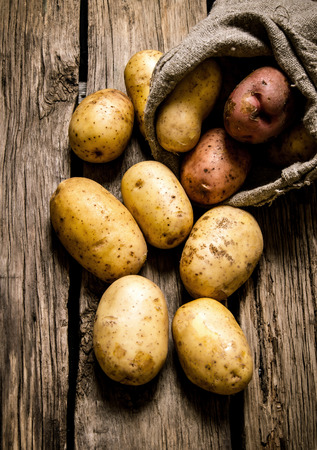 Raw potato food . Fresh potatoes in an old sack on wooden background . Stock Photo