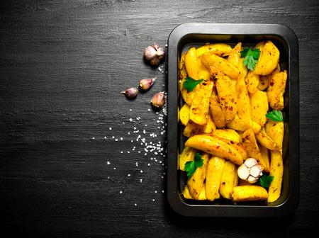 papas: alimentos de patata. patatas cocidas al horno con especias y la sal de mesa de madera negro. Espacio libre para el texto. Vista superior Foto de archivo