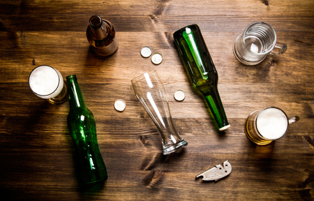 bottle cap opener: Chaos beer on a wooden table. Bottles and glasses of beer . Top view Stock Photo