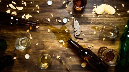 맥주 파티. 파티에 쏟은 맥주, 병 뚜껑 및 남은 칩이 식탁에 있습니다. 평면도