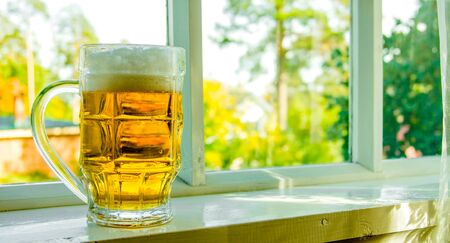 windowsill: Glass of fresh beer on  the windowsill in summer.