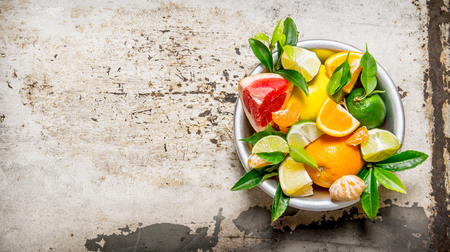 Sliced citrus fruits - grapefruit, orange, tangerine, lemon, lime  leaves in a cup.  On rustic background. Free space for text . Top view