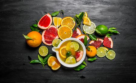 Het sap van citrusvruchten - grapefruit, sinaasappel, mandarijn, citroen, limoen in een Cup. Op een zwarte houten achtergrond. Bovenaanzicht