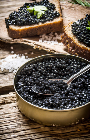 salty: Sandwiches with black caviar, a jar of caviar and a spoon. On a wooden table.