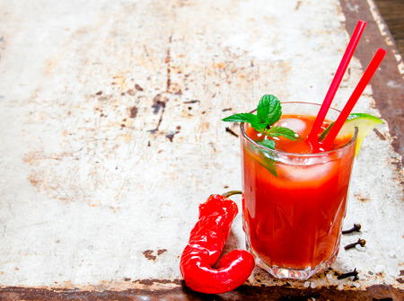 bloody: The cocktail bloody mary . Cocktail made of tomatoes, vodka, ice, lime, pepper , salt on rustic background . Free space for text. Stock Photo