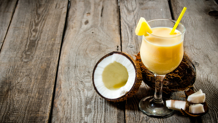 Cocktail Pina colada. A fresh cocktail in a glass with coconut on wooden table. Free space for text.