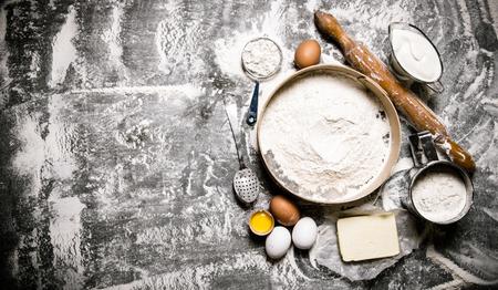 원단의 제조. 반죽을위한 재료 - 롤링 핀 체 가루, 사우어 크림, 버터, 계란. 돌 테이블에. 텍스트에 대 한 여유 공간. 평면도 스톡 콘텐츠