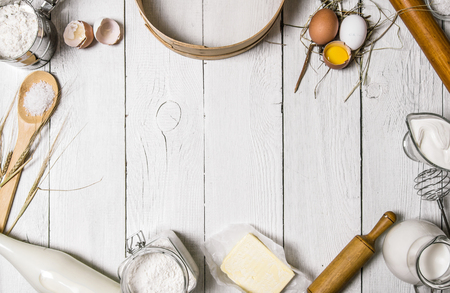 ingredient: Baking background. Ingredients for the dough - Milk, eggs, flour, sour cream, butter, salt and different tools. On a white wooden background. Free space for text . Top view Stock Photo