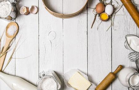 masa: hornear de fondo. Ingredientes para la masa - leche, huevos, harina, crema agria, mantequilla, sal y diferentes herramientas. Sobre un fondo de madera blanca. Espacio libre para el texto. Vista superior