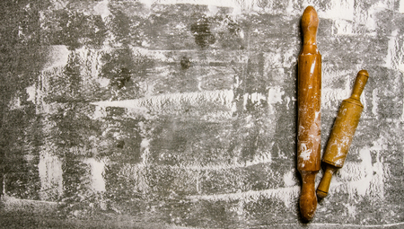 pastry: Baking background with the rolling pin with flour. On the stone table. Free space for text . Top view