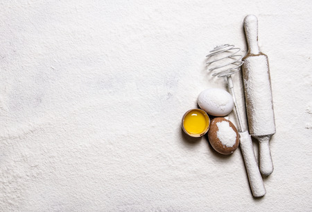 flour: Preparation of the dough. Eggs with venicom and rolling pin in flour.  Free space for text . Top view