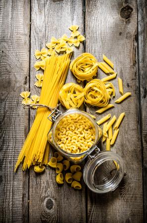 pastas: La pasta seca en latas y se mezcla la pasta con espaguetis. En el fondo de madera. Vista superior Foto de archivo