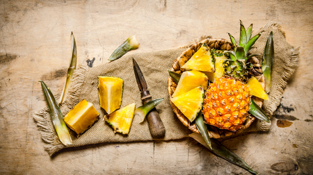slice: Fresh pineapples, whole and sliced in a basket on old fabric. On a wooden table. Top view