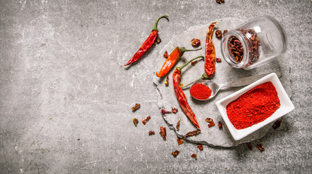 Ground red Chili pepper in a bowl and spoon on a stone stand. On the stone table. Free space for text . Top view