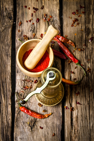 The old mill and mortar with ground red chili pepper. On wooden background. Top view Stock Photo