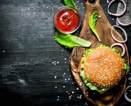 vegetable background: The Burger and the fresh ingredients on the old Board. On a black chalkboard.  Top view.