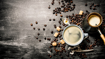 Fresh coffee in a Cup with beans and cane sugar around. On black rustic background.
