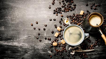 Frischer Kaffee in einer Tasse mit Bohnen und Rohrzucker um. Auf schwarzem Hintergrund rustikalen. Standard-Bild - 53000241