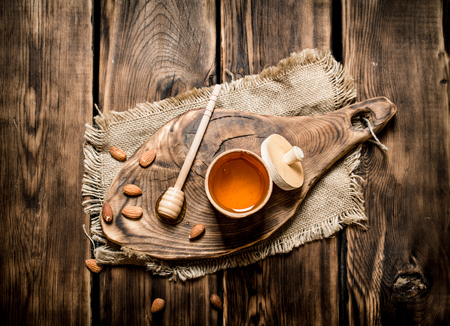 wooden stick: Sweet honey in the barrel on a wooden Board. On wooden background.