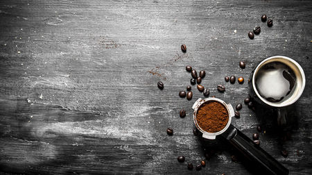 Fresh coffee. Coffee cup with roasted grains . On black rustic background.