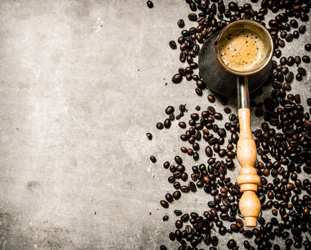 non alcoholic beverage: Coffee pot and roasted coffee around. On a stone background. Stock Photo