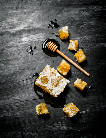 honey comb: Honey background. Natural honey comb and a wooden spoon . On black rustic table.