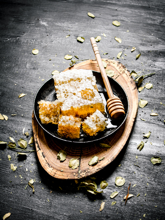 honey comb: honey background. Natural honey comb with herbs on a wooden trunk. On black rustic background. Stock Photo