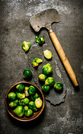 stone cutter: Brussels sprouts with a hatchet. On a stone background.