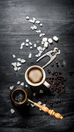 brewed: Freshly brewed coffee with crystalline sugar. On black rustic background.