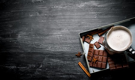 hot chocolate: chocolate caliente con canela y chocolate amargo. Rústico de fondo negro.