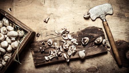 hatchet: Cutting fresh mushrooms old hatchet. On wooden background.