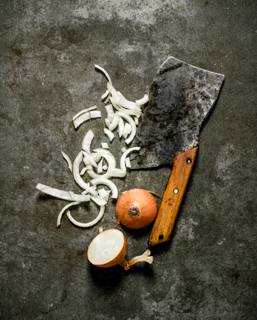 stone cutter: chopped onion with an old hatchet. On a stone background.