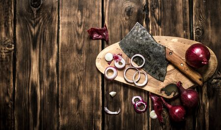 hatchet: Sliced red onion and an old hatchet. On wooden background. Stock Photo
