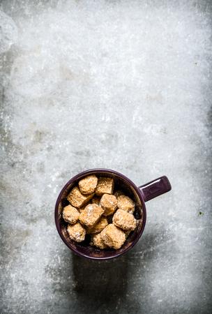cane sugar: Mug with dark cane sugar. On a stone background.