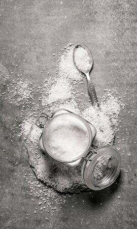 a jar stand: Salt background. Jar of salt and a lot of salt around. On a stone background. Stock Photo