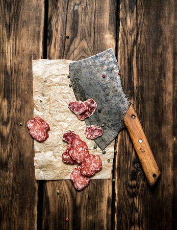 hatchet: Sliced salami and an old hatchet. On a wooden background.