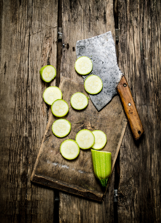 hatchet: Sliced zucchini and an old hatchet . On wooden background.