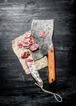 hatchet: Salami with garlic and an old hatchet . On black rustic background. Stock Photo